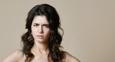 Picture of angry young woman standing isolated over beige background. Looking camera.