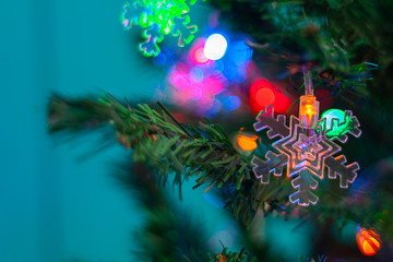 Christmas background. Christmas tree toy in the form of transparent snowflakes on a branch of a Christmas tree, on a highly blurred turquoise background with bokeh. Selective focus.