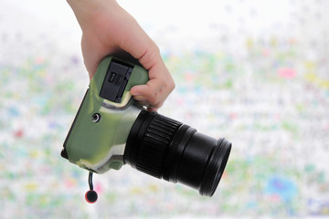 Right hand holding camera DSLR wear silicone camouflage pattern.