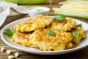 Cutlets from grains of canned corn with parsley on a plate. Wooden background.