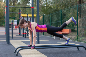 Young caucasian woman workouts on the park sports ground. In sports plank position with one leg up, sportswear. White earphones, protective gloves. Real woman in morning excersice. Copy space, outdoor - fototapety na wymiar