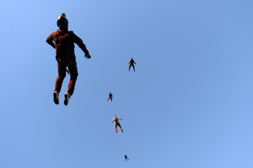 A flock of skydivers is in the sky.