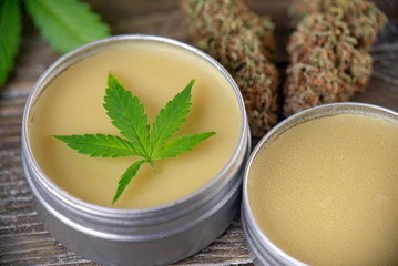 Cannabis hemp cream with marijuana leaf and nug on wood surface