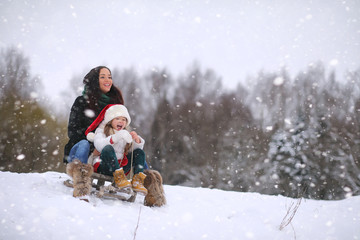 A winter fairy tale, a young mother and her daughter ride a sled in the forest. A girl on a sled with gifts on the eve of the new year in the park.