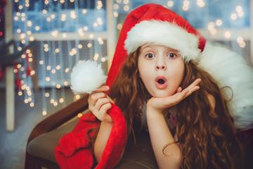 Surprised baby in Santa hat.