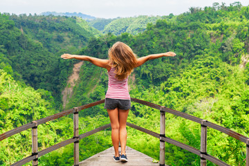 Family vacation lifestyle. Young woman stand on edge of overhanging bridge on high cliff. Happy girl looking at stunning tropical jungle view. Tukad Melangit is popular travel destination in Bali.