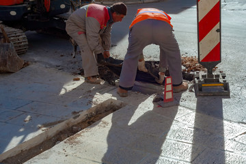 Execution of fiber optic distribution network for telecommunications. Workers position the cast iron manhole covers on manholes