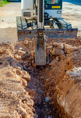 excavation with a narrow section to bury corrugated plastic cable ducts for the production of a fiber optic telecommunication cable distribution network.