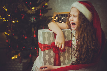 Sad child girl in Santa hat.