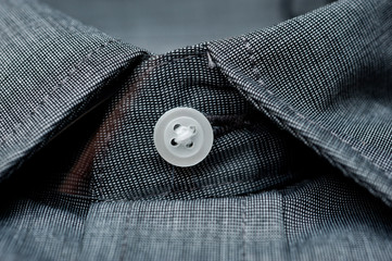 Texture of dark gray shirt fabric with white buttons close-up shot