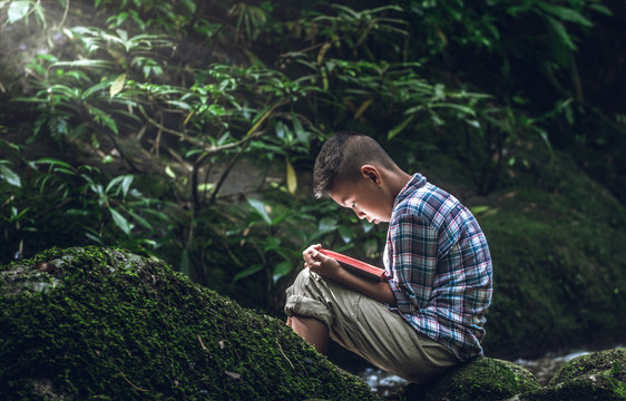 Boy reading book or holy bible in nature with little light.Children and religion.