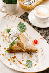 Rolled crepes served with mint leaves, whipped cream and caramel syrup on white plate
