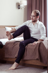 Businessman wearing glasses taking his shoes off after difficult day