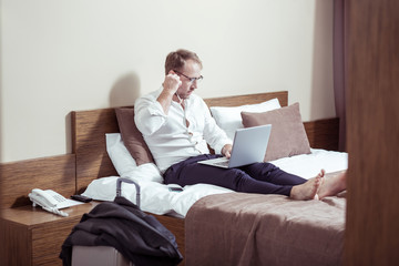 Blonde-haired businessman using earphones for video chat in hotel room