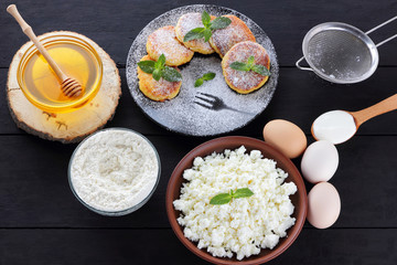 Cottage cheese pancakes and ingredients for their preparation on dark background. Syrniki with honey and mint on plate. Ingredients for cooking: flour, cottage cheese, eggs, sour cream, honey