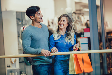 Happy young couple shopping and holding bags