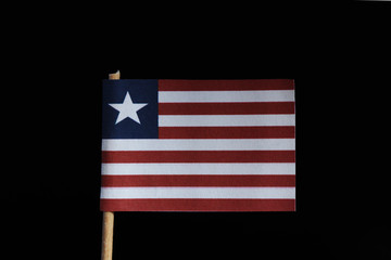 A official flag of Liberia on toothpick on black background. Consists of eleven horizontal stripes alternating red and white, in the canton a white star on a blue field