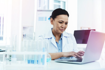 Joyful positive woman sitting in front of the laptop