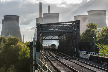 A Freight Train Crossing A Bridge In Front Of A Power Station