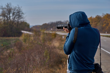 Tourist at the highway with a camera, photographs nature. travel concept concept.