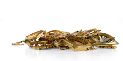 A scrap of gold. Old and broken jewellery, watches of gold and gold-plated isolated on a white background.