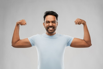 power, strength, sport and people concept - happy young indian man showing biceps over grey background