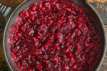 Traditional cranberry sauce in black cast-iron skillet, top view