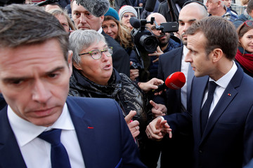 French President Emmanuel Macron talks with residents before the weekly cabinet meeting at the Ardennes Prefecture in Charleville-Mezieres