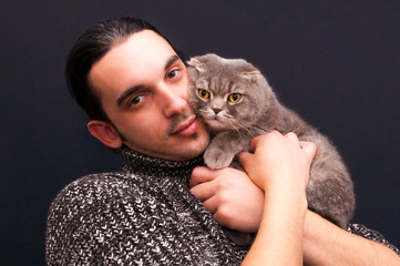 Portrait of brunette man holding face to face a gray hair Scottish Fold yellow-eyed male cat