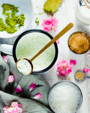 Matcha colorful latte with spoon and milk pot, flowers on white wooden background. Trendy detox healthy drink
