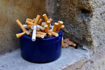 Blue ashtray full of cigarette butts on stone window