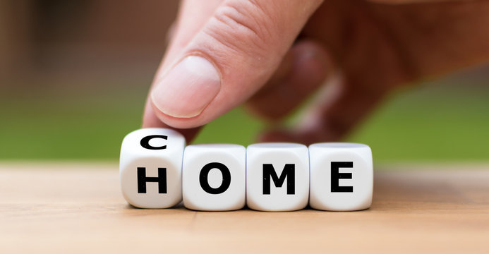 """Hand is turning a dice and changes the word """"come"""" to """"home"""""""