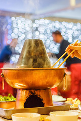 Chinese traditional hot pot with a hand with chopsticks