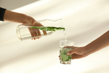 Woman pouring fresh cucumber water from bottle into glass on light background