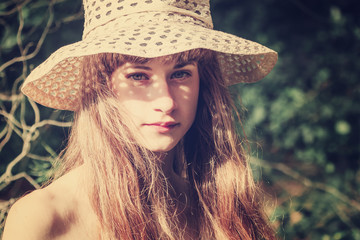 Outdoor portrait of young beautiful serious girl with long hair, wearing straw hat, posing near blooming tree