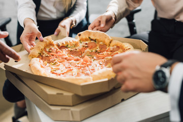 close-up partial view of coworkers eating pizza in office