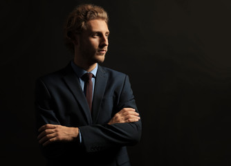 Young businessman with crossed arms against black background