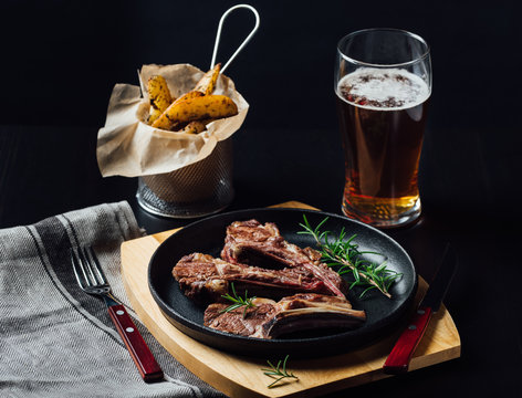 Grilled lamb chops in a cast-iron frying pan with fried potatoes and glass of beer on dark background