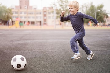 active lifestyle in a modern city - little boy playing with a soccer ball at the stadium