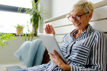 Smiling beautiful senior woman using digital tablet at home