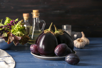Fresh eggplants with plums on color wooden table