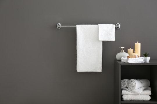 White bath towels near grey wall