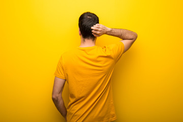 Man on isolated vibrant yellow color on back position looking back while scratching head