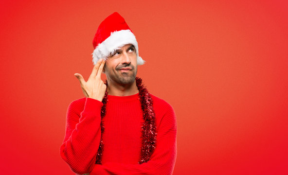 Man with red clothes celebrating the Christmas holidays with problems making suicide gesture on red background