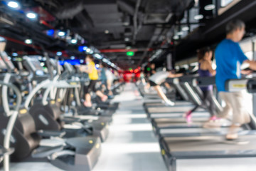 Blurred of fitness gym center interior background with two rows of cardio machine