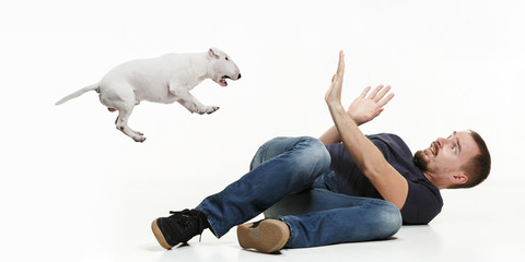 Emotional Portrait of scared man and his dog, concept of friendship and care of man and animal. Bull Terrier type Dog on white studio background Wall mural
