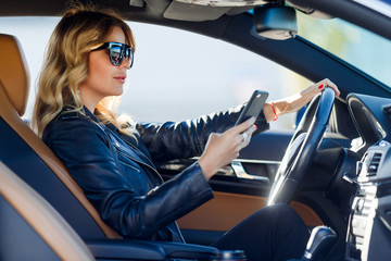 Photo of side blonde in black glasses with cell phone sitting in car