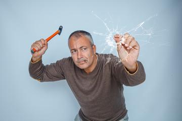 uomo incapace tenta di piantare chiodo sul vetro
