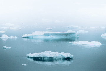 Minimalist blue icebergs in the fog