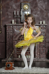 girl in a yellow ballet dress with vintage phone is talking